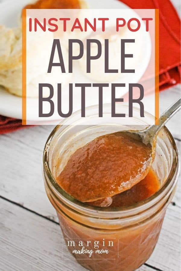 Jar of Instant Pot apple butter, with a spoon removing a scoop