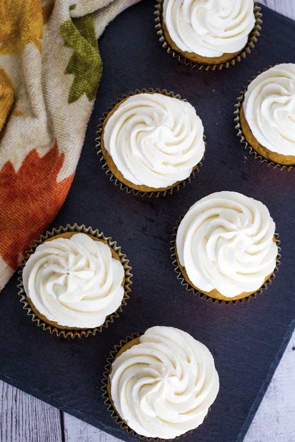 Six pumpkin cupcakes topped with ermine frosting