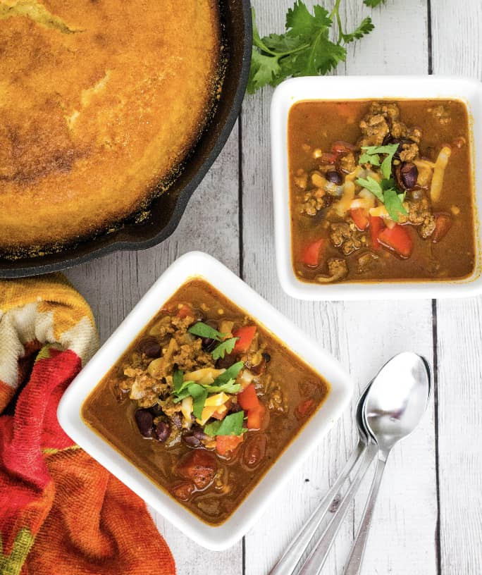 two bowls of Instant Pot pumpkin chili next to a cast iron skillet of cornbread