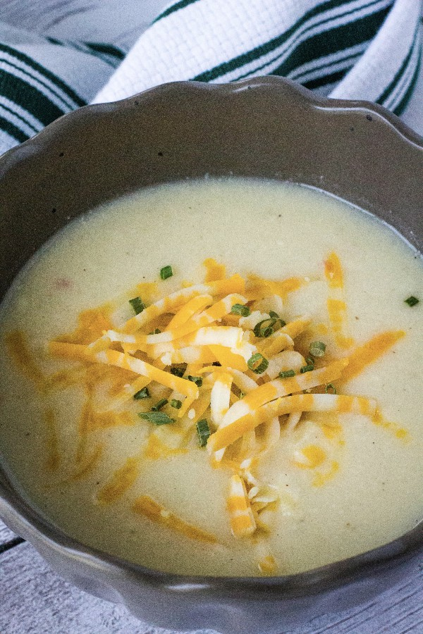 brown bowl filled with cheesy cauliflower soup, topped with shredded cheese and chives