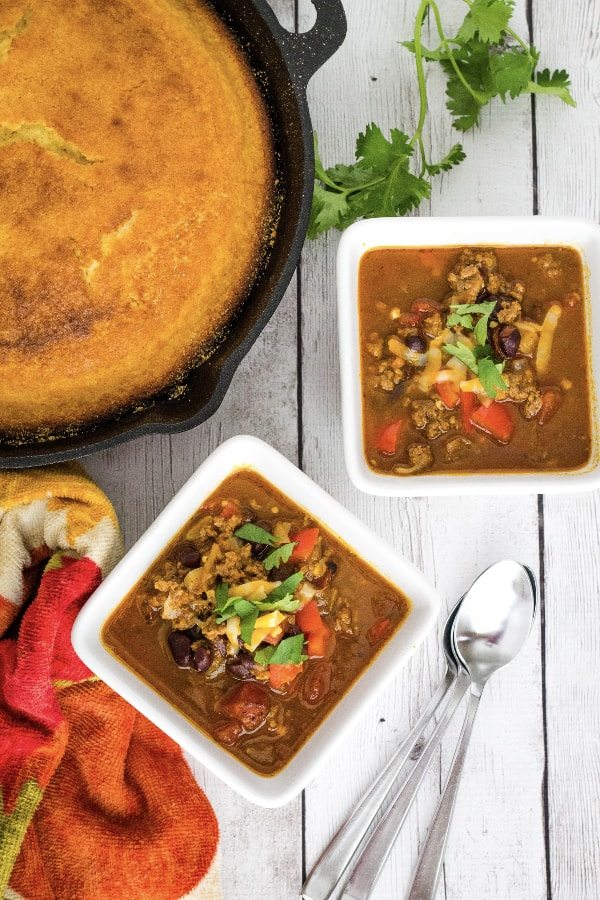 two bowls of Instant Pot pumpkin chili next to a skillet of cornbread and a stack of spoons