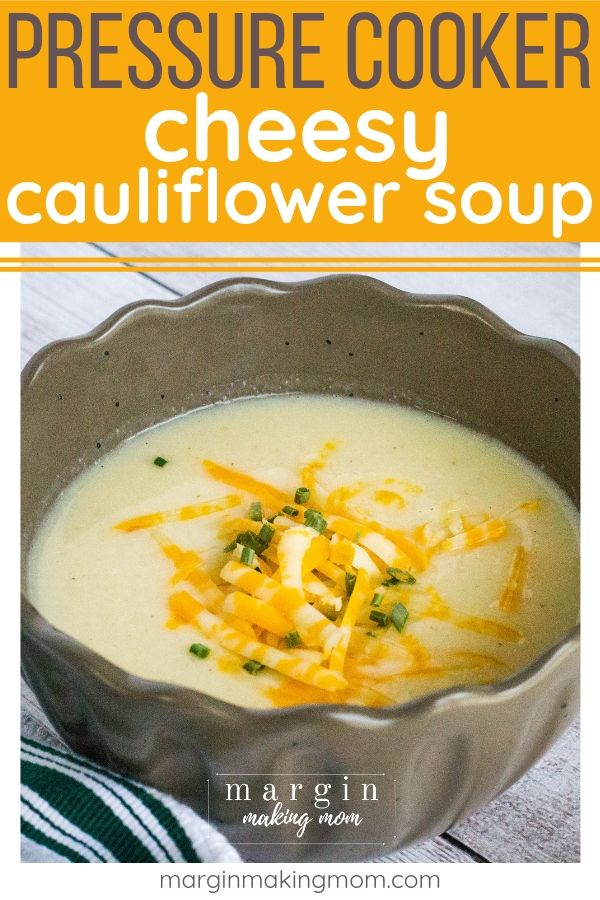 cauliflower soup that was cooked in the pressure cooker, served in a brown bowl and topped with snipped chives and shredded cheese
