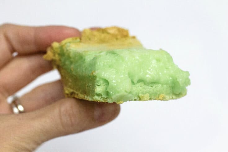 pistachio buttercake square being held by a woman's hand