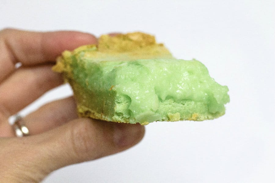 a woman's hand holding a square of pistachio ooey gooey butter cake