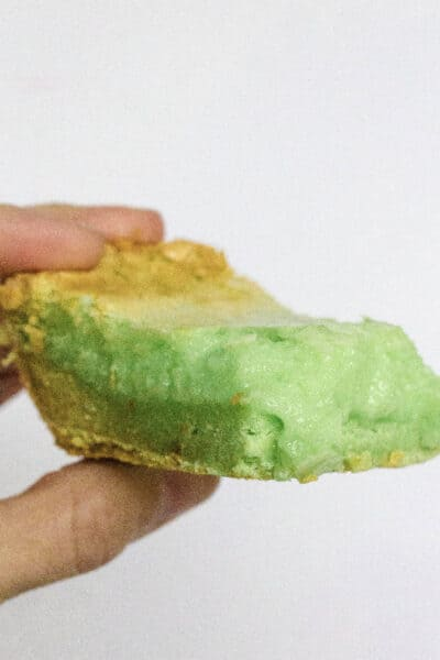 pistachio ooey gooey butter cake bar being held by a woman's fingers