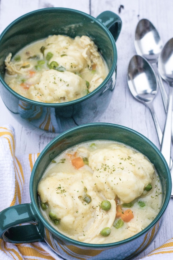 Two green soup mugs filled with chicken and drop dumplings.
