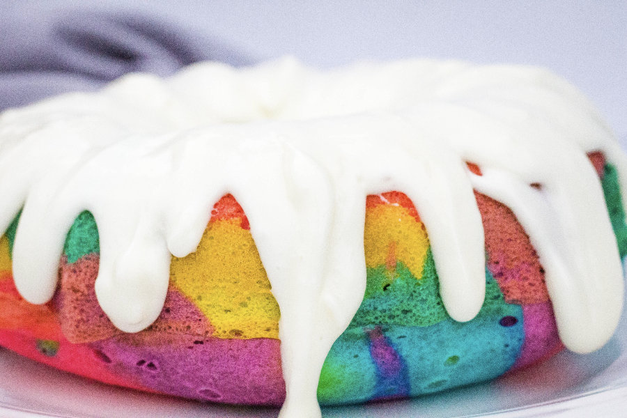 Rainbow bundt cake topped with cream cheese glaze