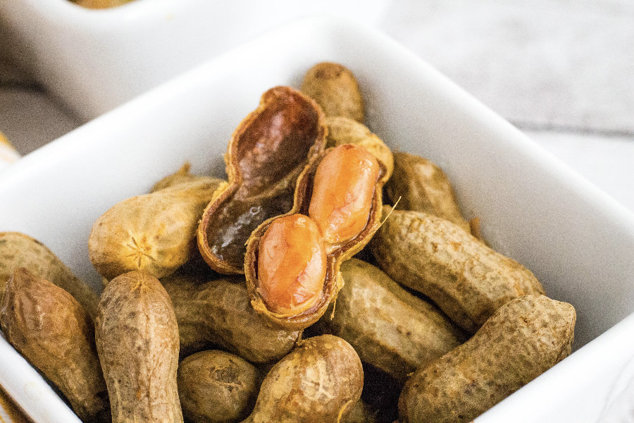 Cajun boiled peanuts with a shell open, displaying the tender peanuts inside