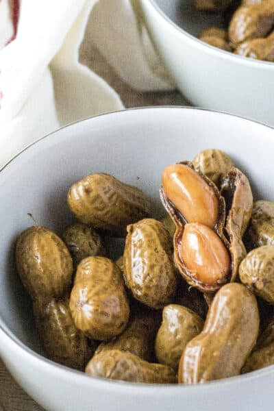white bowl filled with boiled peanuts in the shell, with one shell opened to reveal the soft peanuts inside