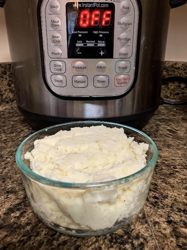 Glass bowl of mashed potatoes in front of an Instant Pot pressure cooker
