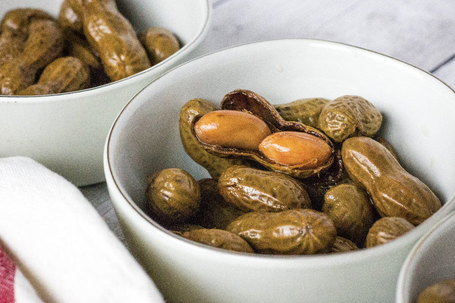 small white bowls filled with boiled peanuts in the shell, with one peanut shell cracked opened to show the tender peanuts inside