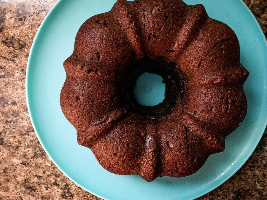 unfrosted chocolate bundt cake on a blue plate