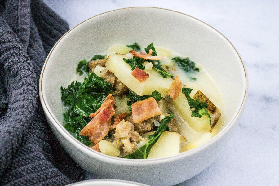 white bowl of healthy zuppa toscana next to a gray kitchen towel