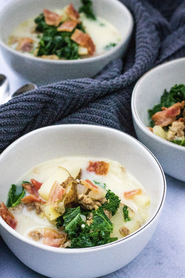 three white bowls filled with healthy zuppa toscana soup, with potatoes, sausage, and kale, topped with bacon crumbles