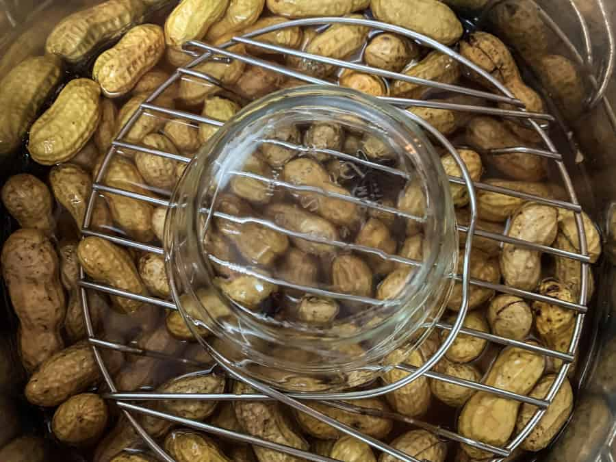 a small Pyrex bowl and trivet on top of the peanuts in the insert pot, weighing them down so they stay submerged