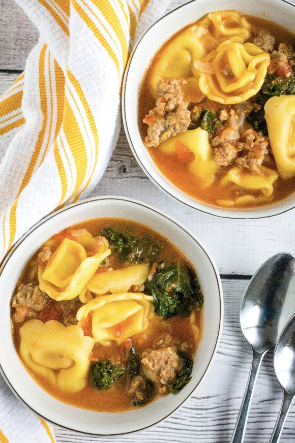 two white bowls filled with Instant Pot tortellini soup