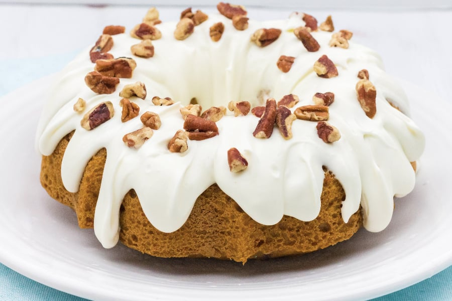 Carrot cake that was baked in the Instant Pot on a white plate, topped with cream cheese frosting and chopped pecans