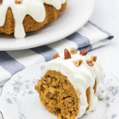 slice of Instant Pot carrot cake on a white and blue plate, with the remaining bundt cake in the background
