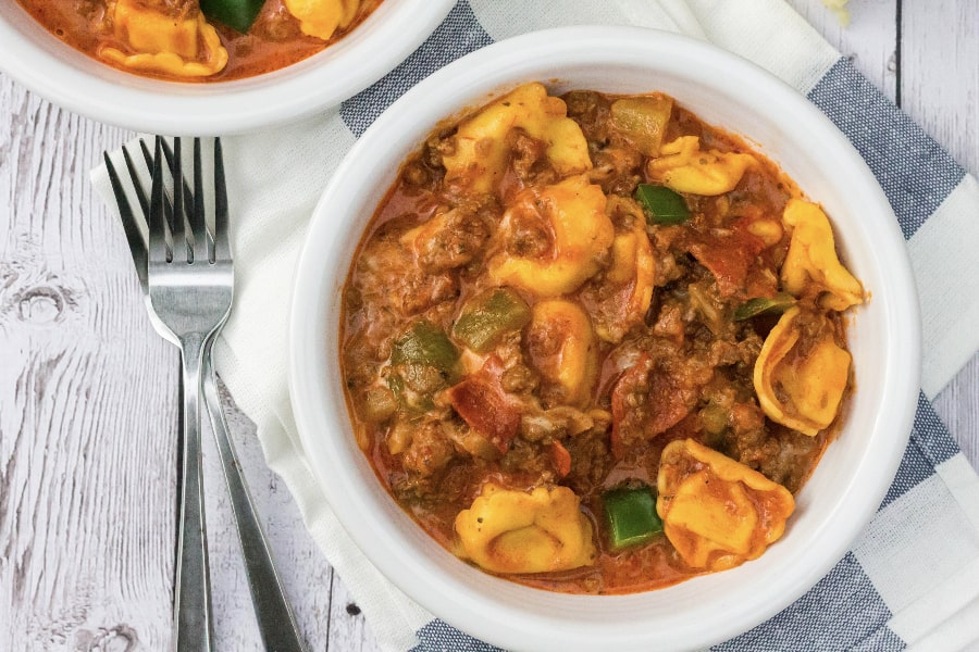 Easy Instant Pot pepperoni pizza tortellini in a white bowl, with forks next to the bowl
