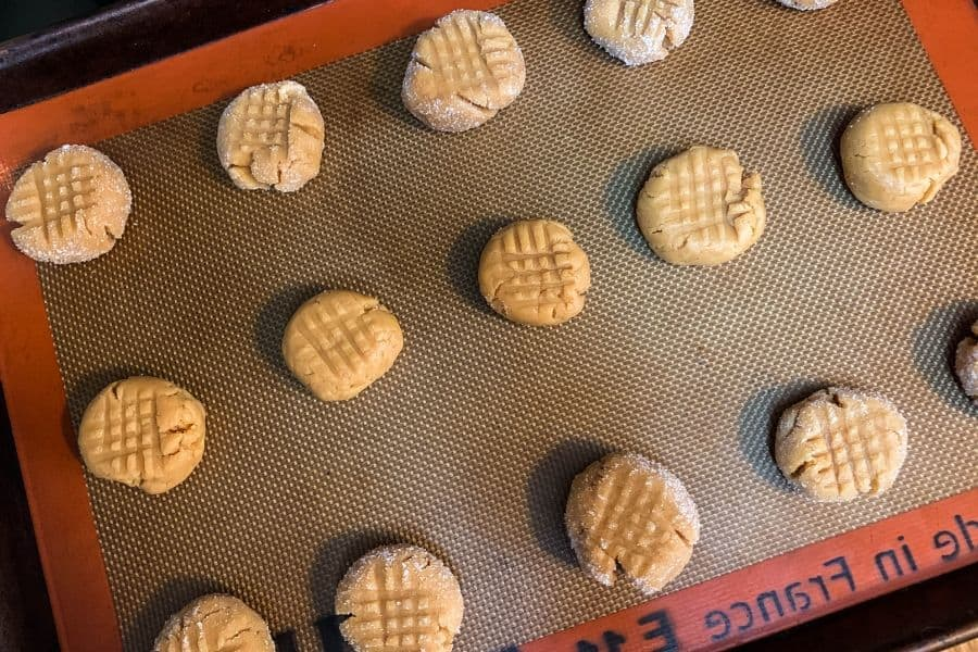 peanut butter cookie dough on a baking sheet, ready to be baked