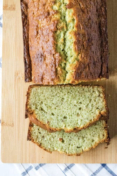 sliced loaf of pistachio banana bread on a light brown cutting board