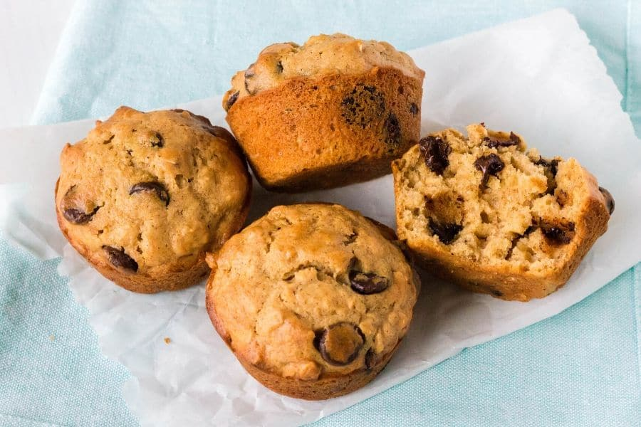 four oatmeal chocolate chip muffins on a piece of parchment paper
