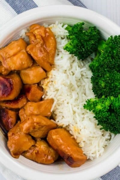 white bowl of teriyaki chicken, rice, and broccoli on a blue and white striped cloth