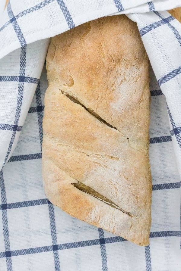 loaf of french bread in a white and blue checkered towel