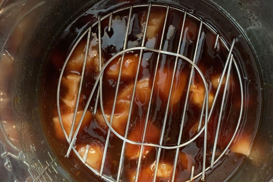 chicken and teriyaki sauce in an insert pot of the Instant Pot, with trivet on the chicken