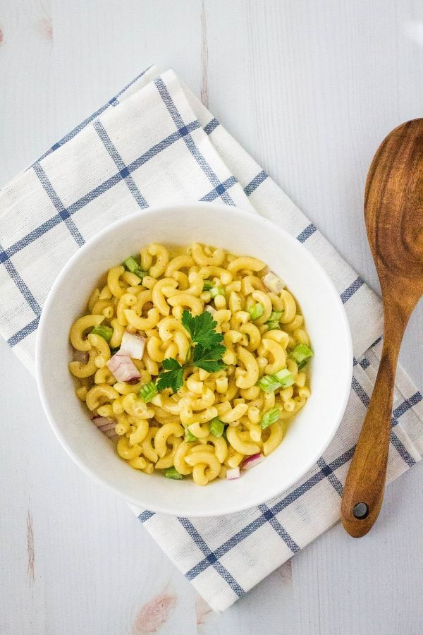 white bowl of Instant Pot Amish macaroni salad next to a wooden serving spoon