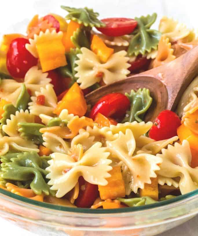 bowl of italian pasta salad with a wooden spoon scooping some out