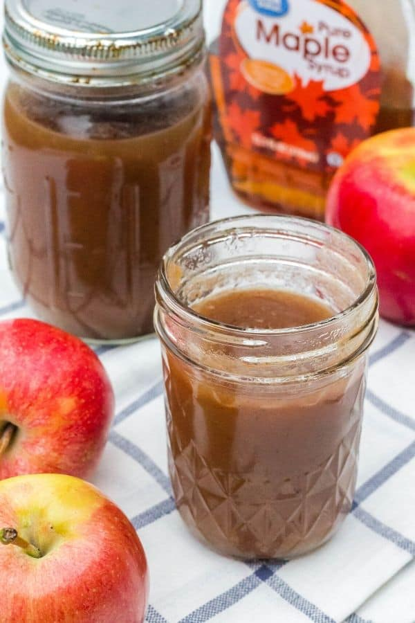 jar of Instant Pot apple butter made with maple syrup, next to some apples