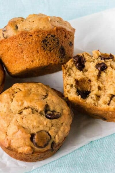 several oatmeal chocolate chip muffins on a piece of parchment paper, with one muffin cut open