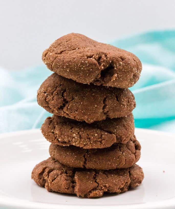 five chocolate snickerdoodles in a stack on a white plate