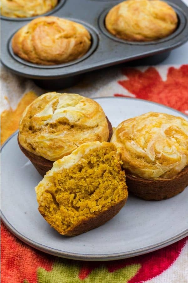 three pumpkin cream cheese muffins on a white plate, with one muffin cut in half to show its soft and moist interior