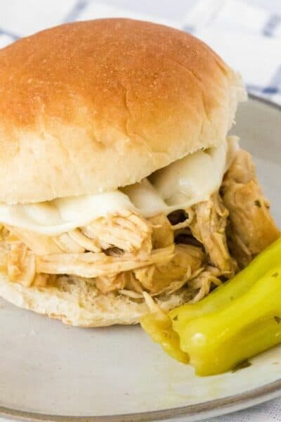 Mississippi chicken sandwich on a plate with a pepperoncini