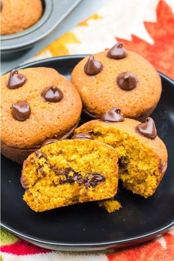 plate of pumpkin chocolate chip muffins, with one muffin cut in half