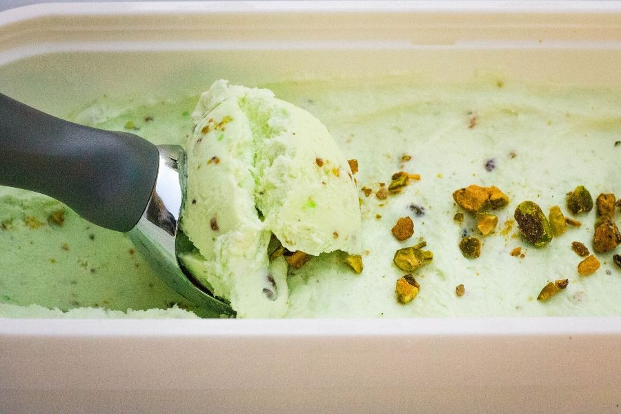 an ice cream scoop is scooping out a curl of pistachio ice cream from the freezer container