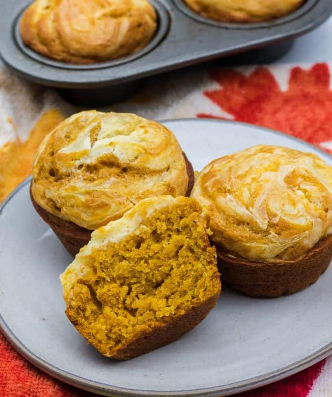 three pumpkin cream cheese muffins on a plate in front of a muffin tin