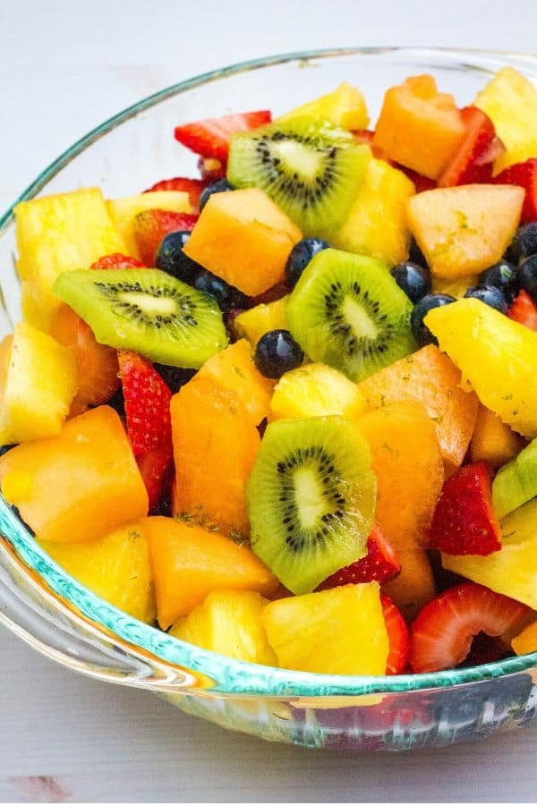 glass bowl full of fruit salad mixed with honey lime dressing