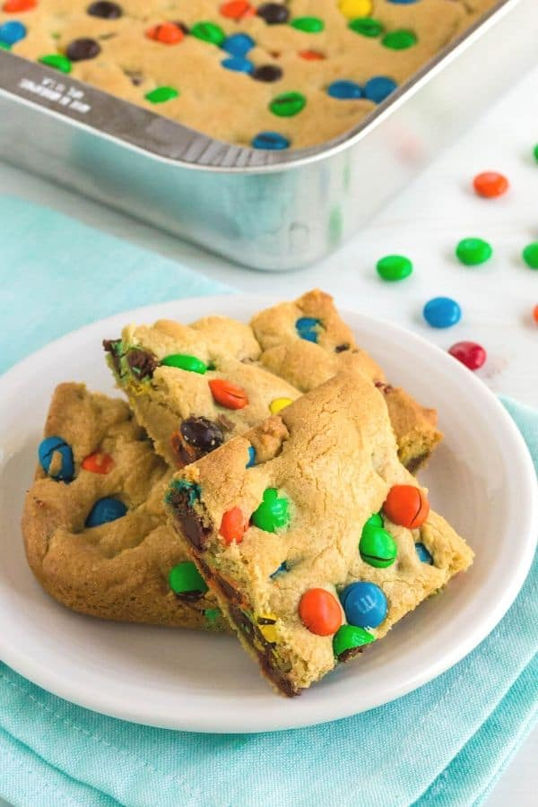 a pan of M&M cookie bars next to a white dessert plate with a few bars on it