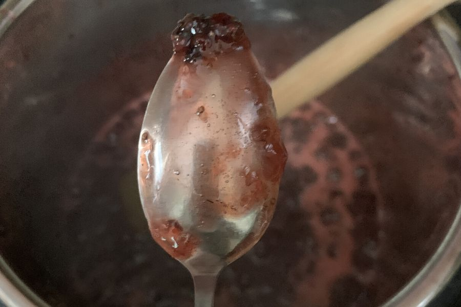 metal spoon with gelled strawberry jam on it, demonstrating the spoon test for jam