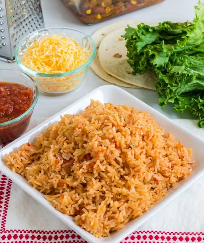 plate of Instant Pot Spanish rice next to other ingredients for a Mexican dinner