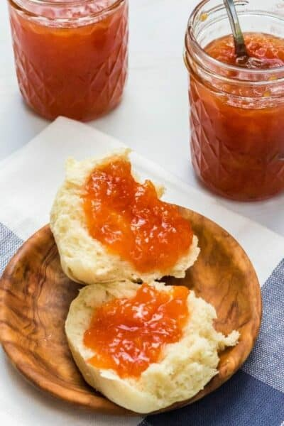 dinner roll with peach jam on it in front of two jars of peach jam