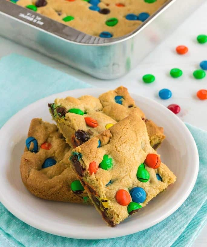 white plate with three M&M Cookie bars on it
