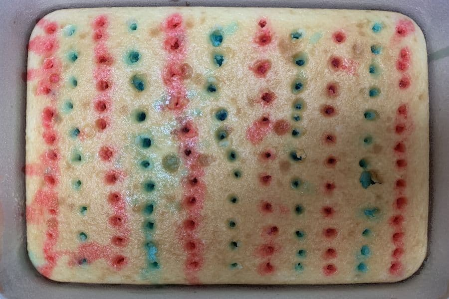 Alternating rows of blue and red Jello in the holes of a poke cake.