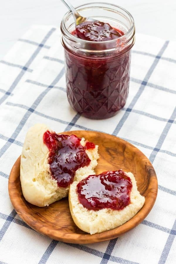 a small wooden plate with a dinner roll on it, with strawberry jam on the dinner roll and the jar of jam in the background