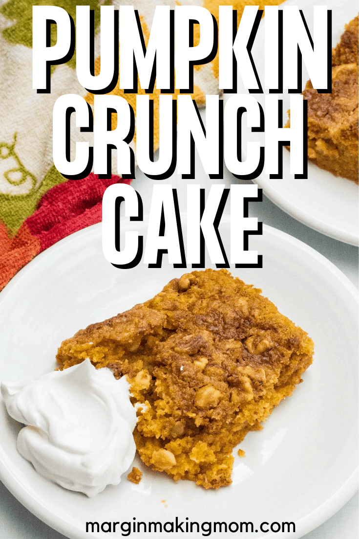 slice of pumpkin crunch cake with a dollop of whipped cream on a white plate
