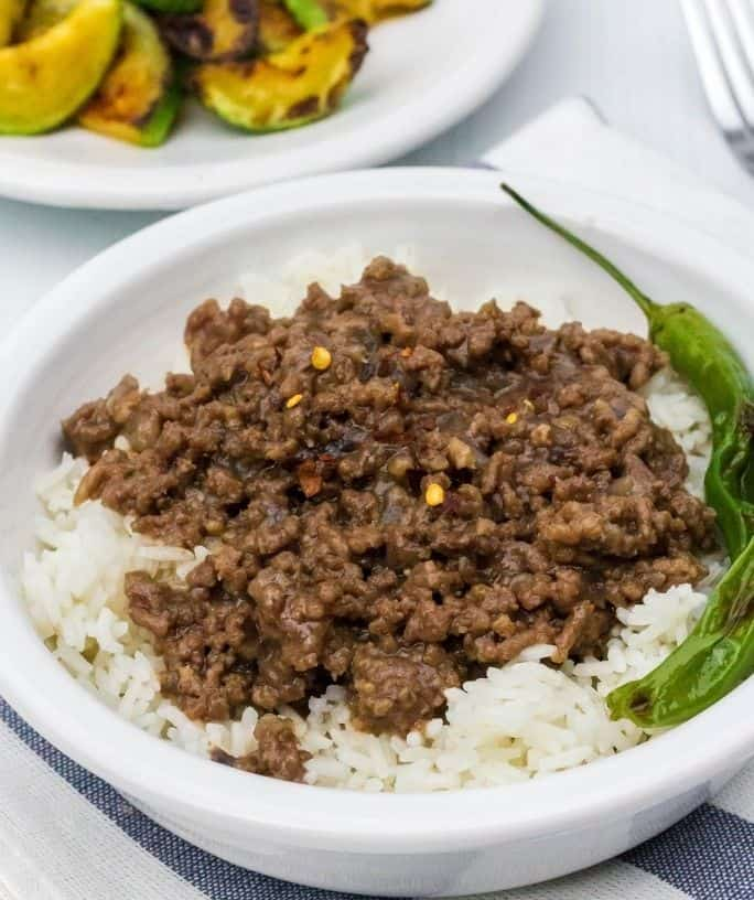 white bowl filled with Instant Pot Korean beef served over white rice, with two shishito peppers in the bowl