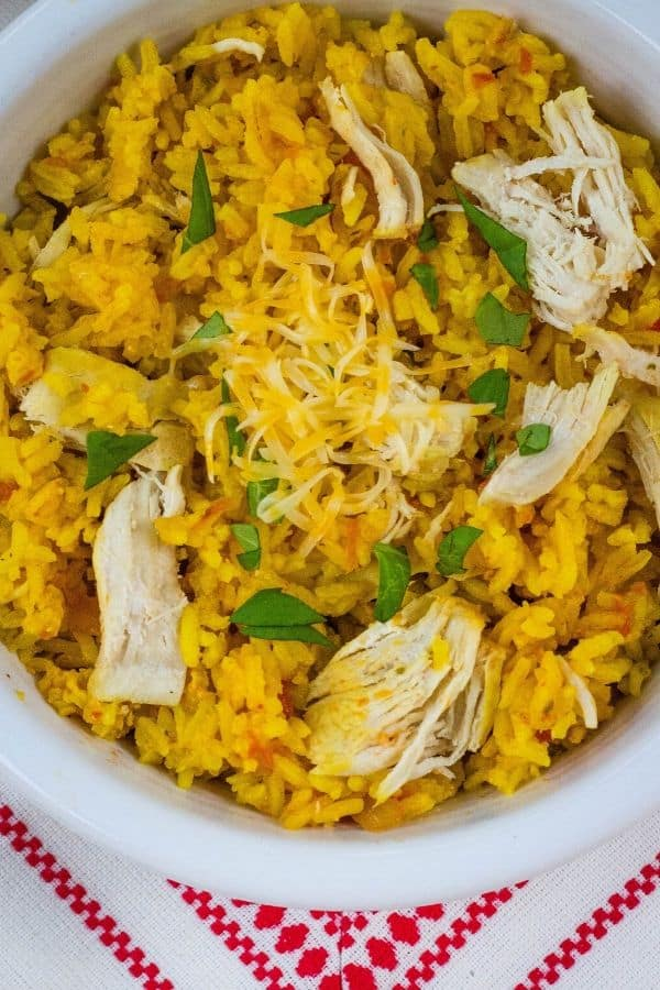 Bowl of pressure cooker arroz con pollo topped with shredded cheese and chopped cilantro